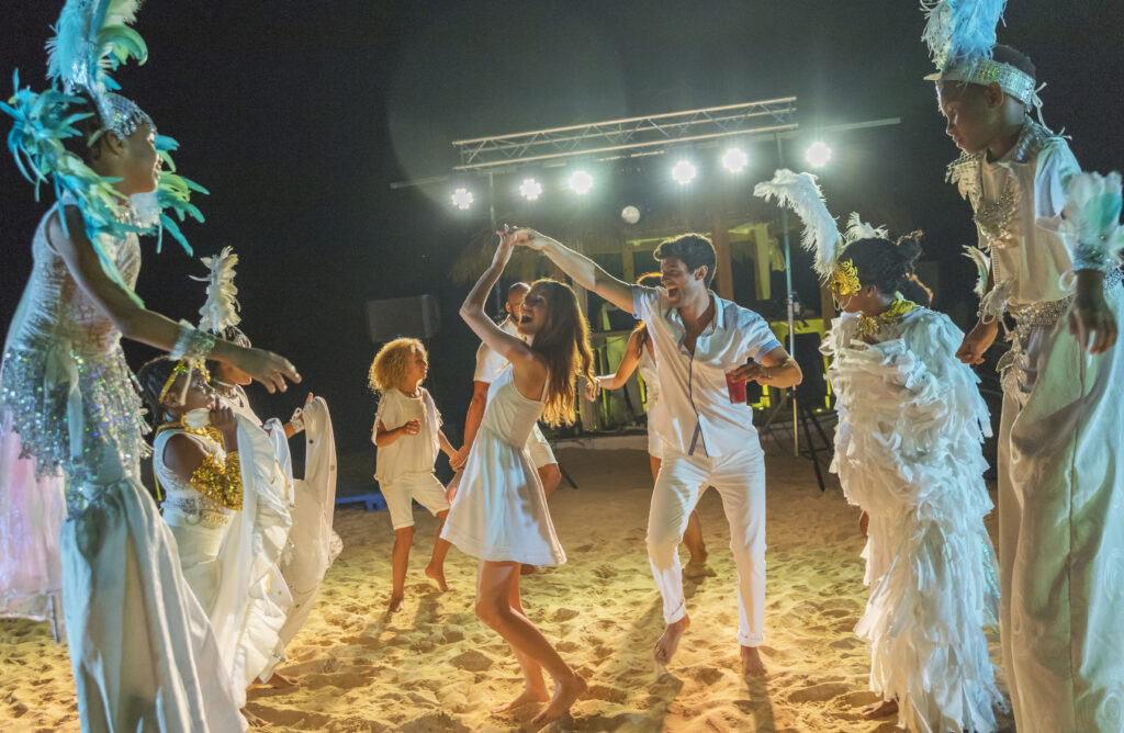 Family learning a cultural dance on the beach in Mexico.