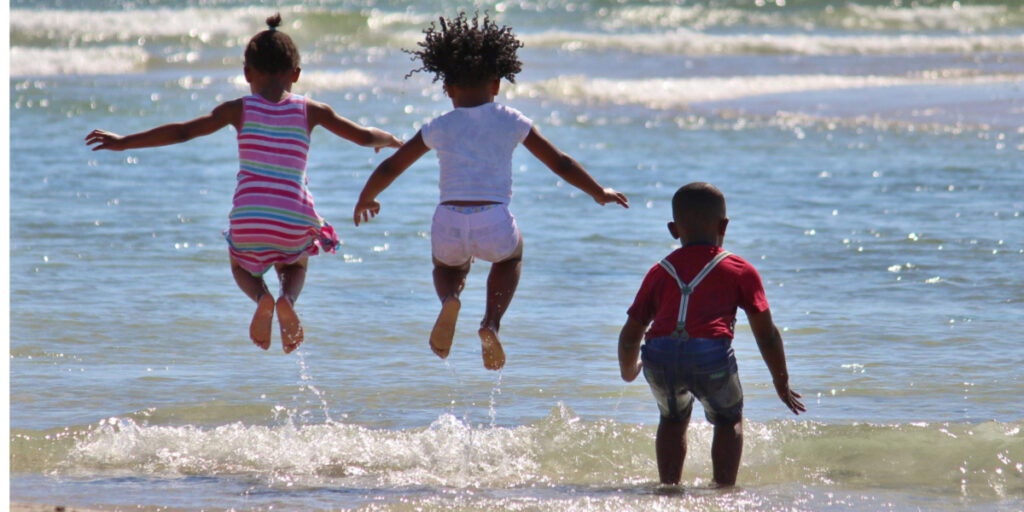 Siblings jumping into the ocean is part of the joy of traveling with your family, even when traveling while Black.