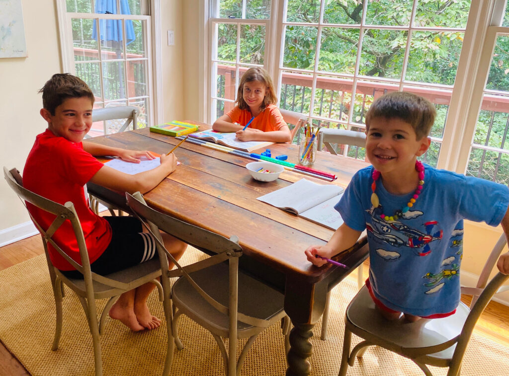 three kids working on lessons at the dining room table