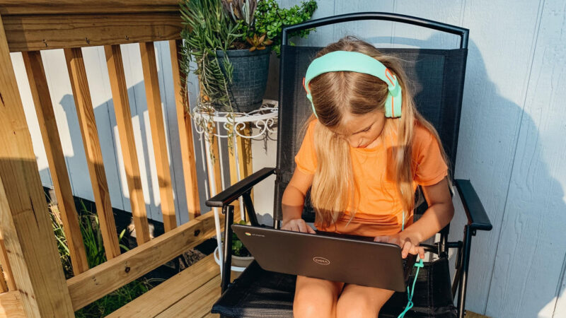 A girl with headphones remote learning on her laptop on the porch