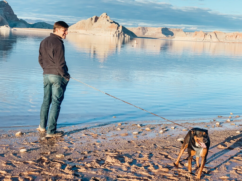 A man standing near a lake with his dog by his side
