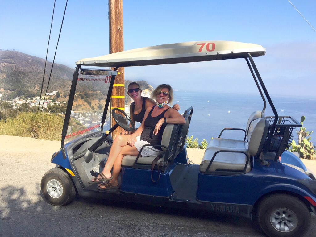 Two women touring Catalina Island in a golf cart, one of the best things to do on catalina island