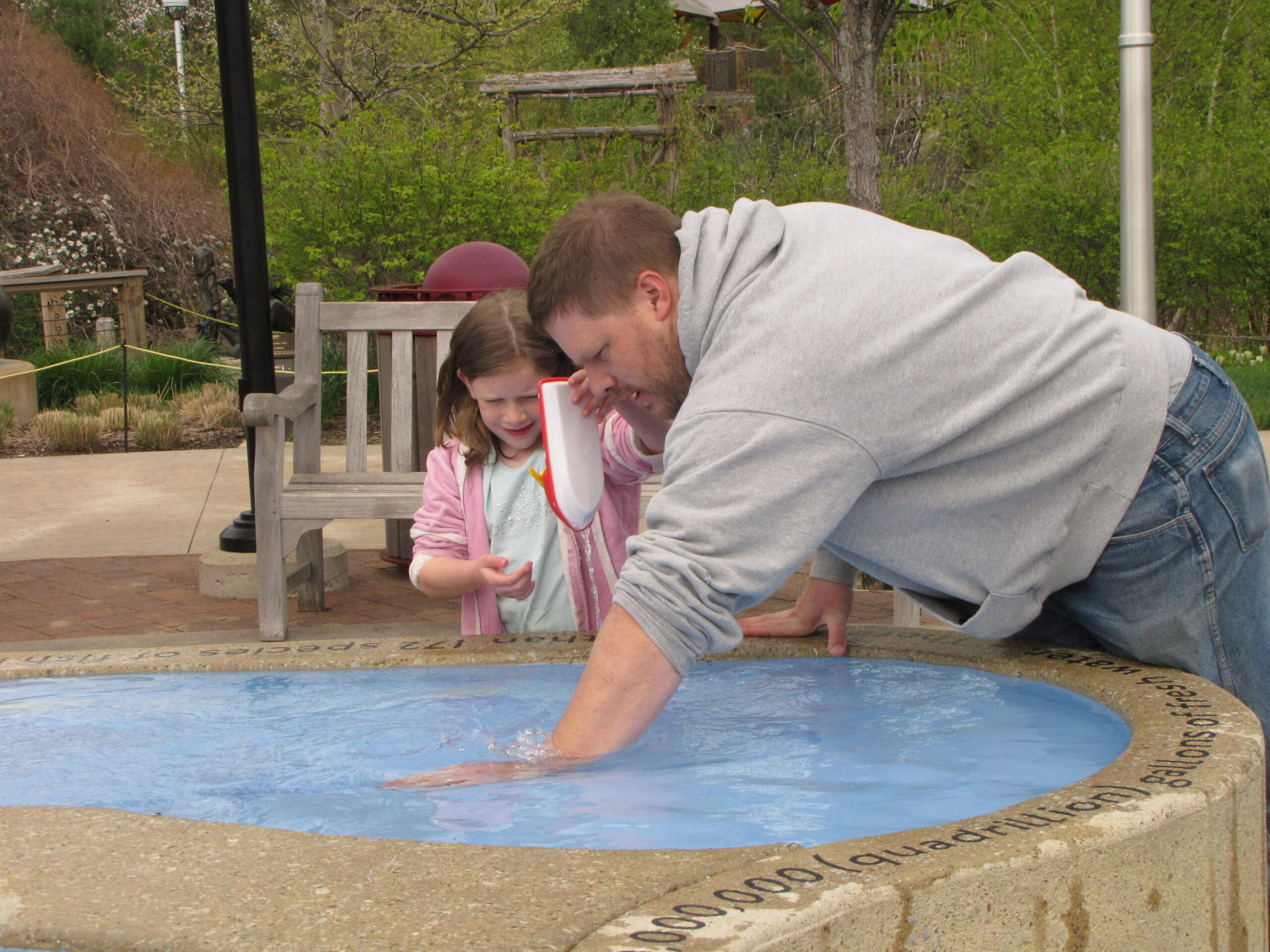 dad and daughter playing in the Great Lakes Garden at Meijer Gardens.