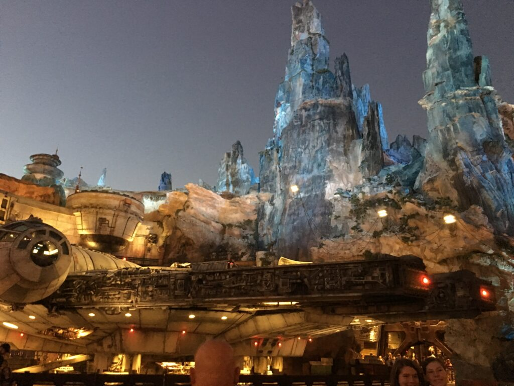star wars galaxys edge disney lit up at dawn against a dark sky