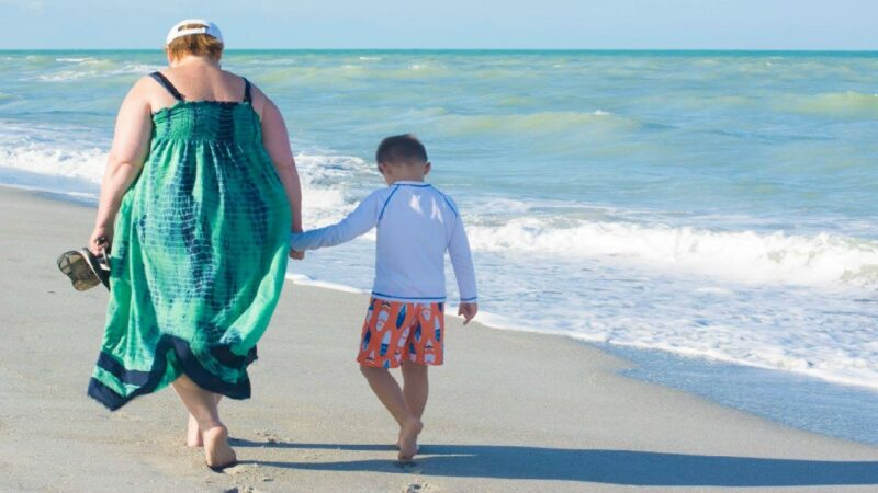 Mom and son walking on a Florida beach