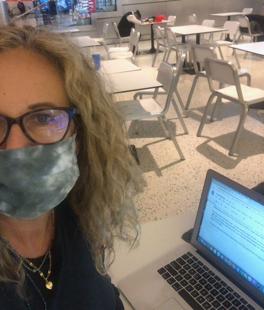 TravelingMom Founder Kim Orlando wearing a face mask in an empty restaurant at JFK airport in New York City.