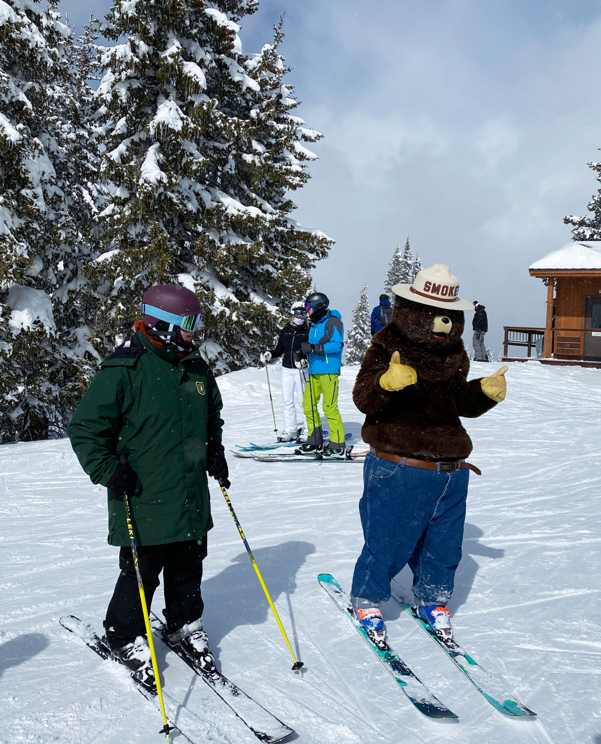 Kid and Smokey the Bear on skis for family ski packing list story
