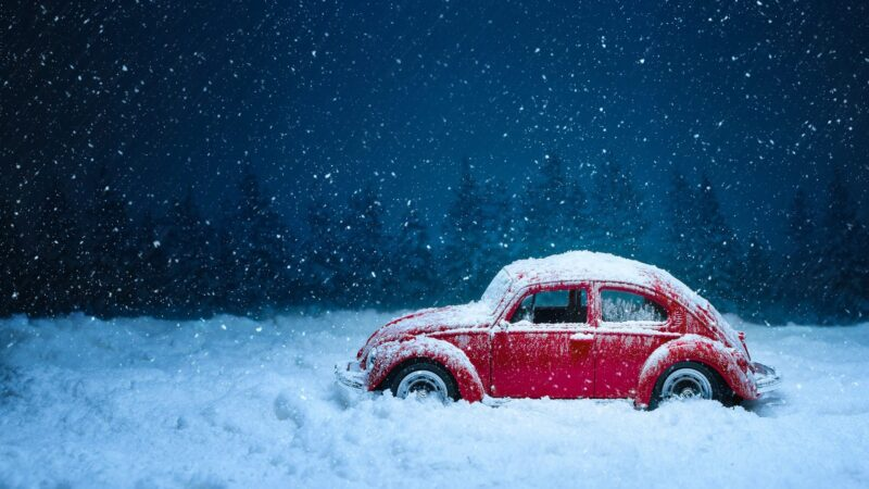 red Volkswagen in the snow during holiday travel