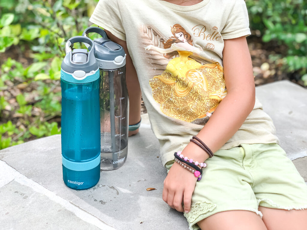 child sitting next to refillable water bottles at Disney World