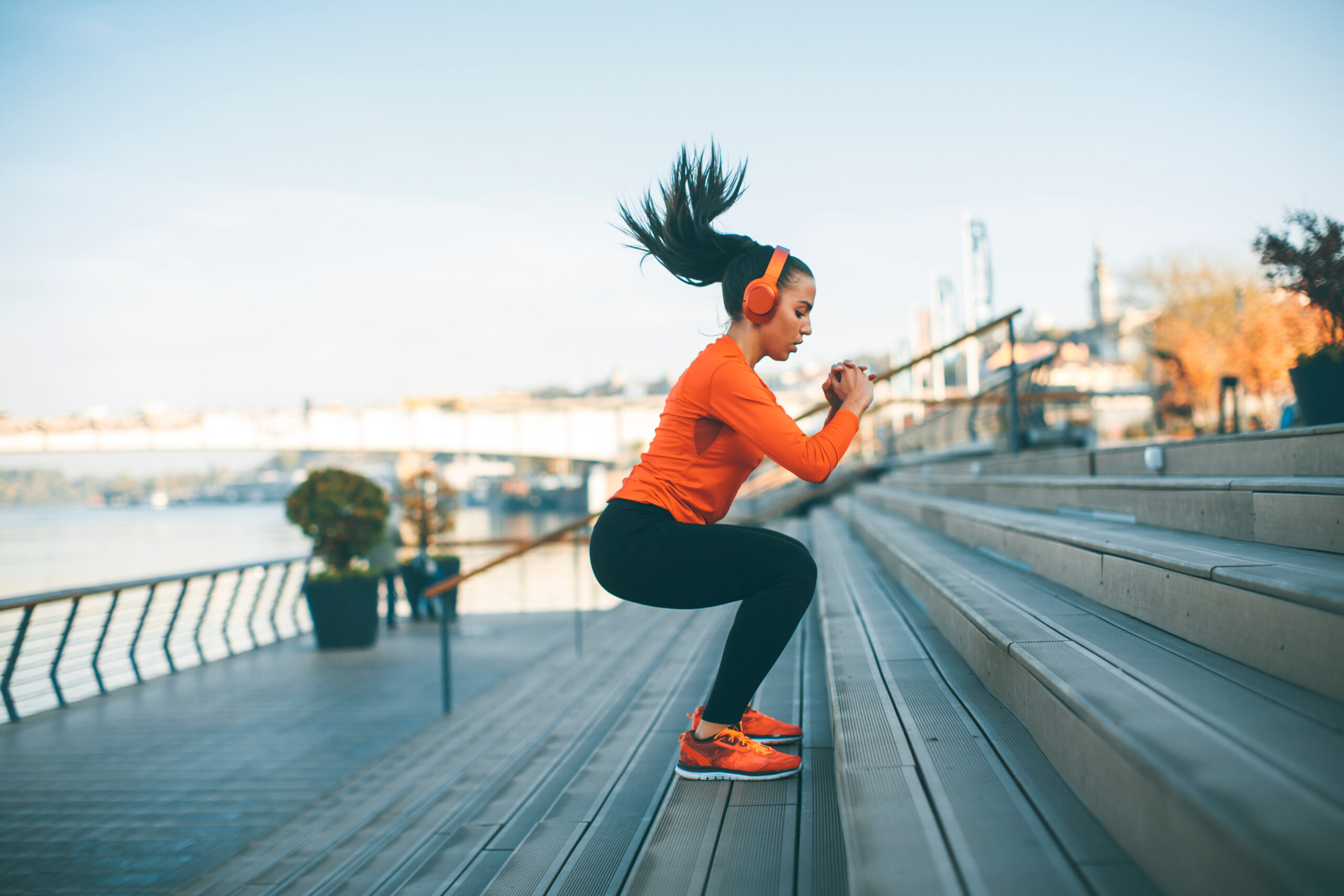 openfit review- woman wearing orange shoes, shirt and headphones with black workout leggings jumping in an outdoor setting