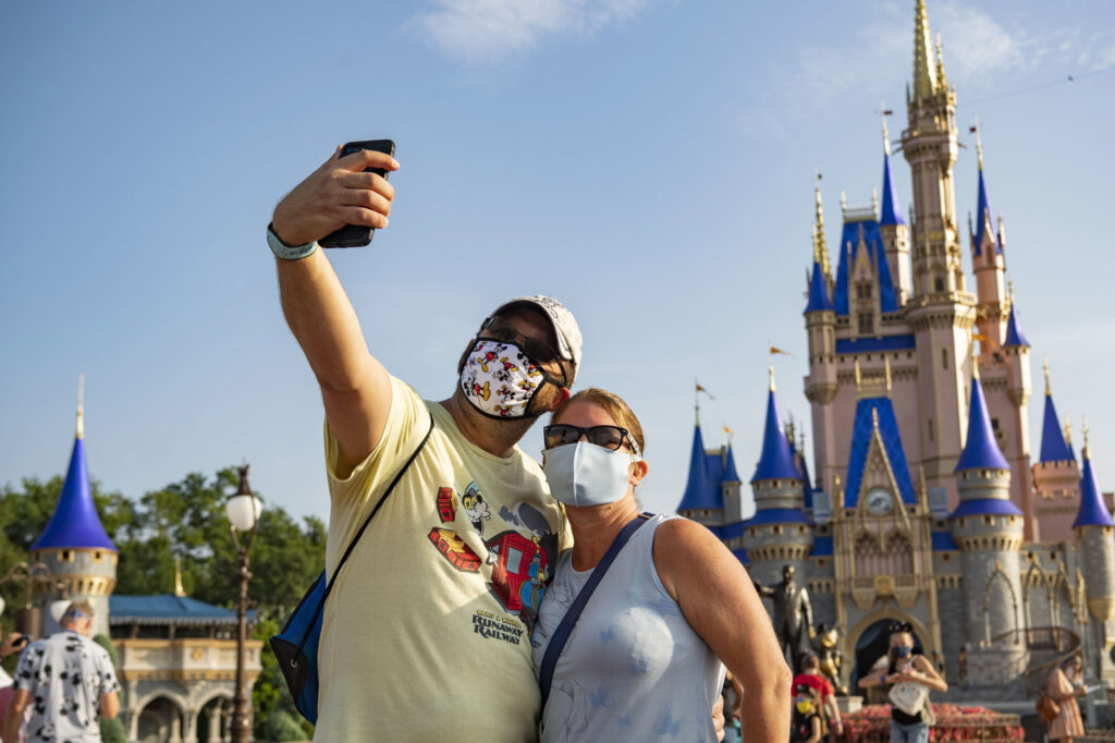 Couple takes a selfie in front of Cinderella Castle during a Disney for adults visit