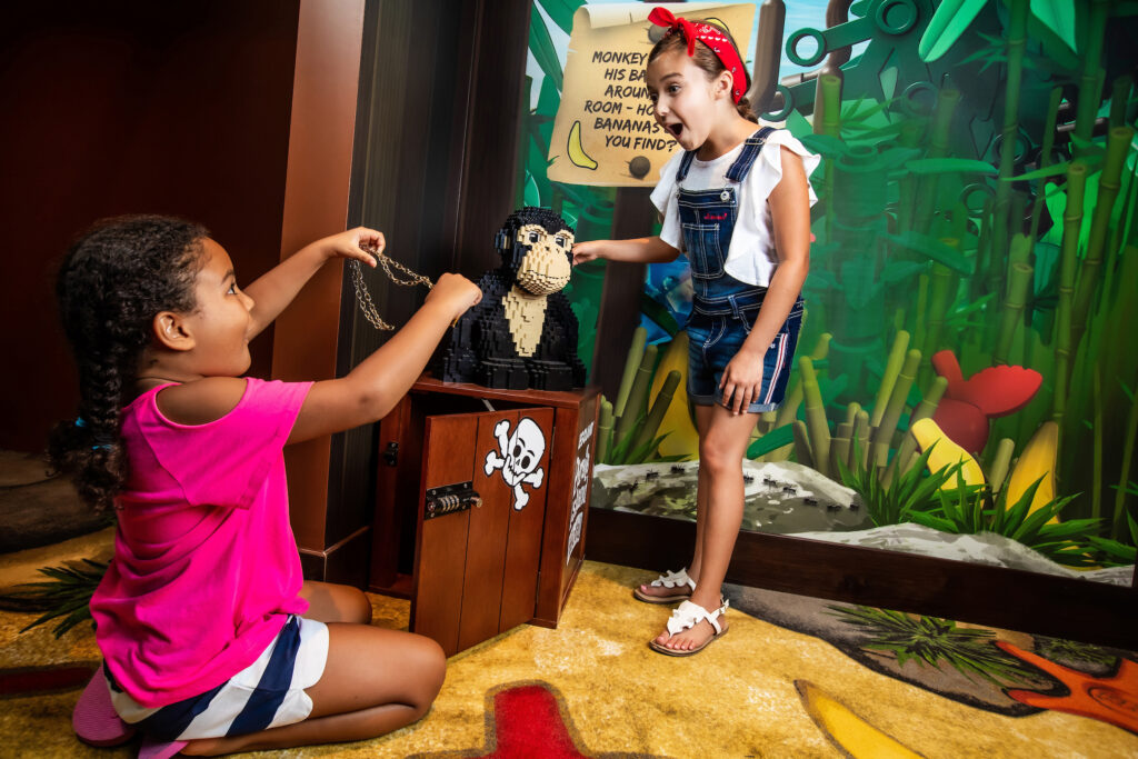 2 girls finding the treasure in a room at the LEGOLAND Pirate Island Hotel.