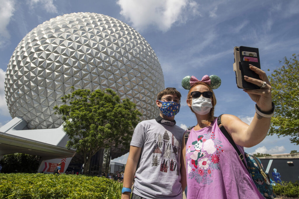 Two teens taking a selfie in front of Spaceship Earth at EPCOT