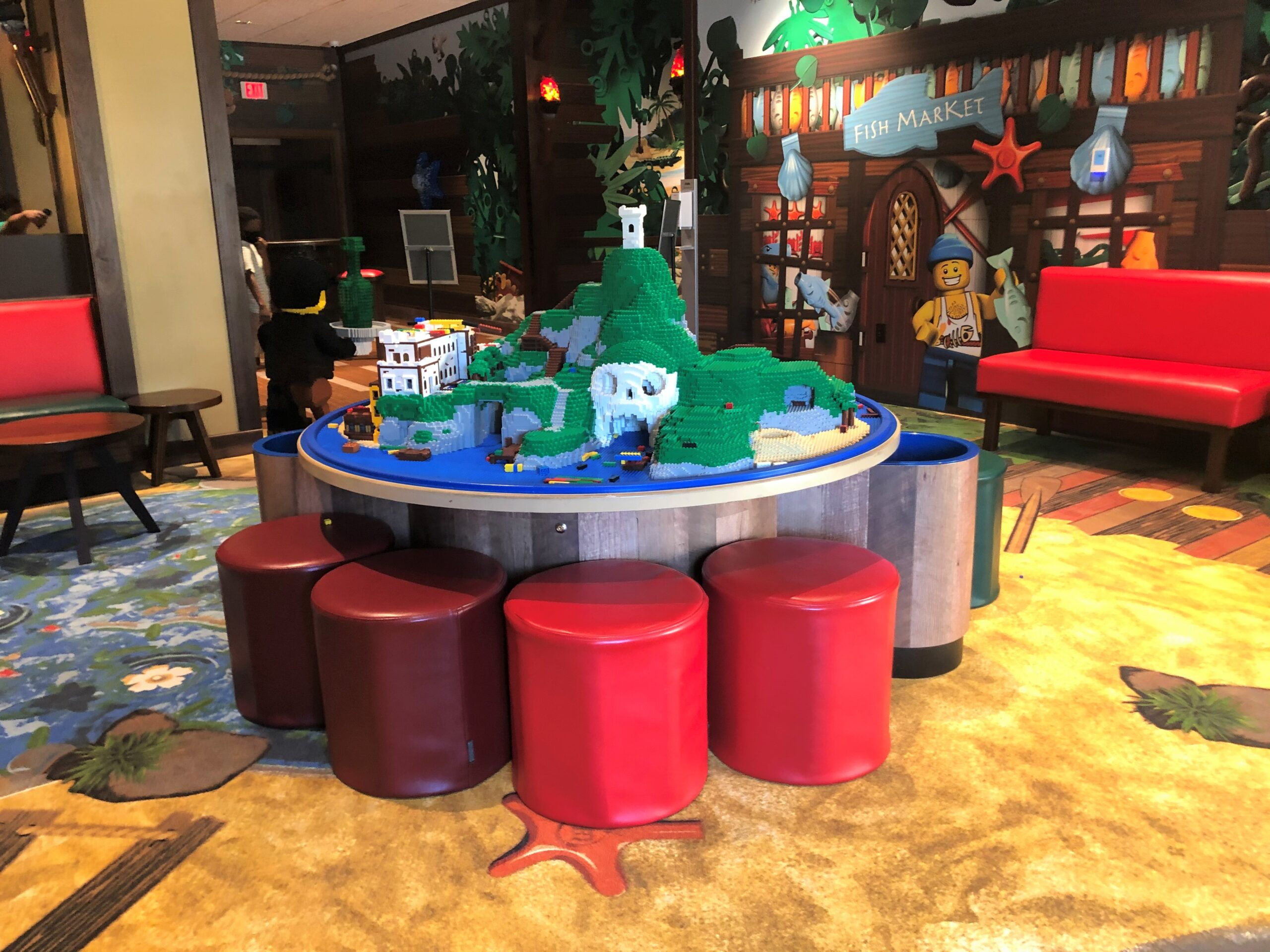 The centerpiece is a huge LEGO play table with a completed LEGO pirate scene.