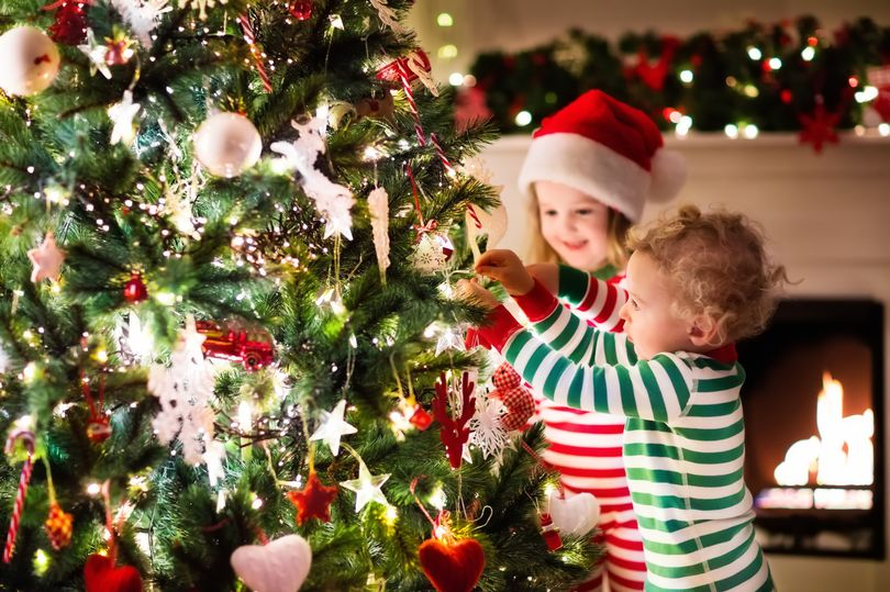 Two small children in front of a Christmas tree