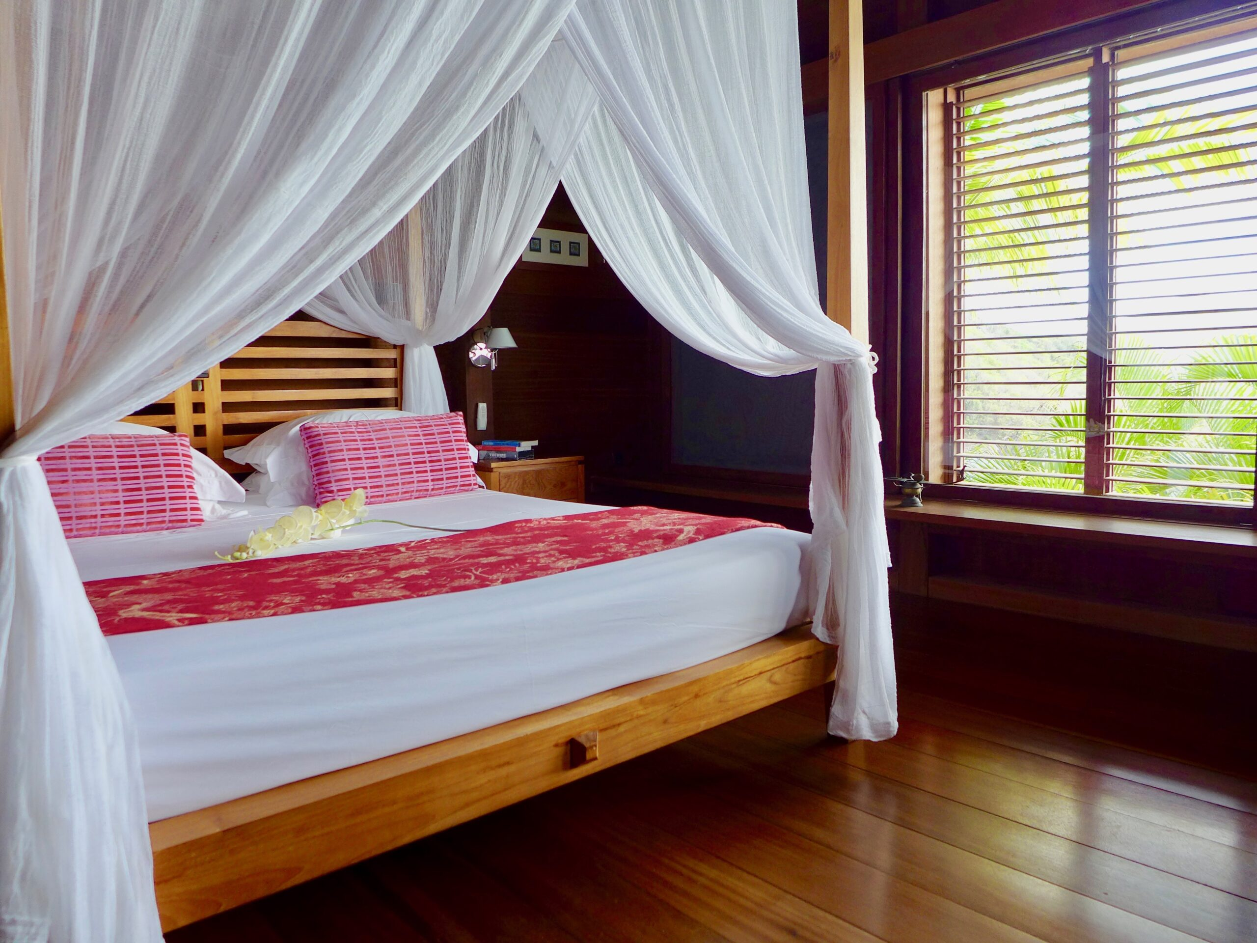 king size bed draped with mosquito netting in caribbean beach house