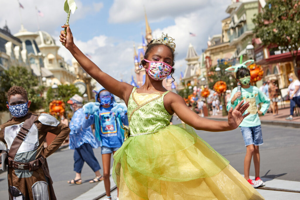 Young girl dressed in a princess costume wearing a Covid mask on Main Street USA in Disney World