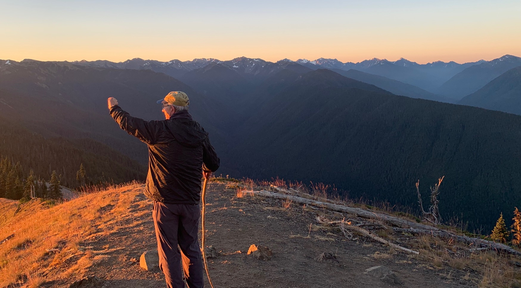 Man shielding eyes from brilliant sunlight at sunset in Olympic National Park