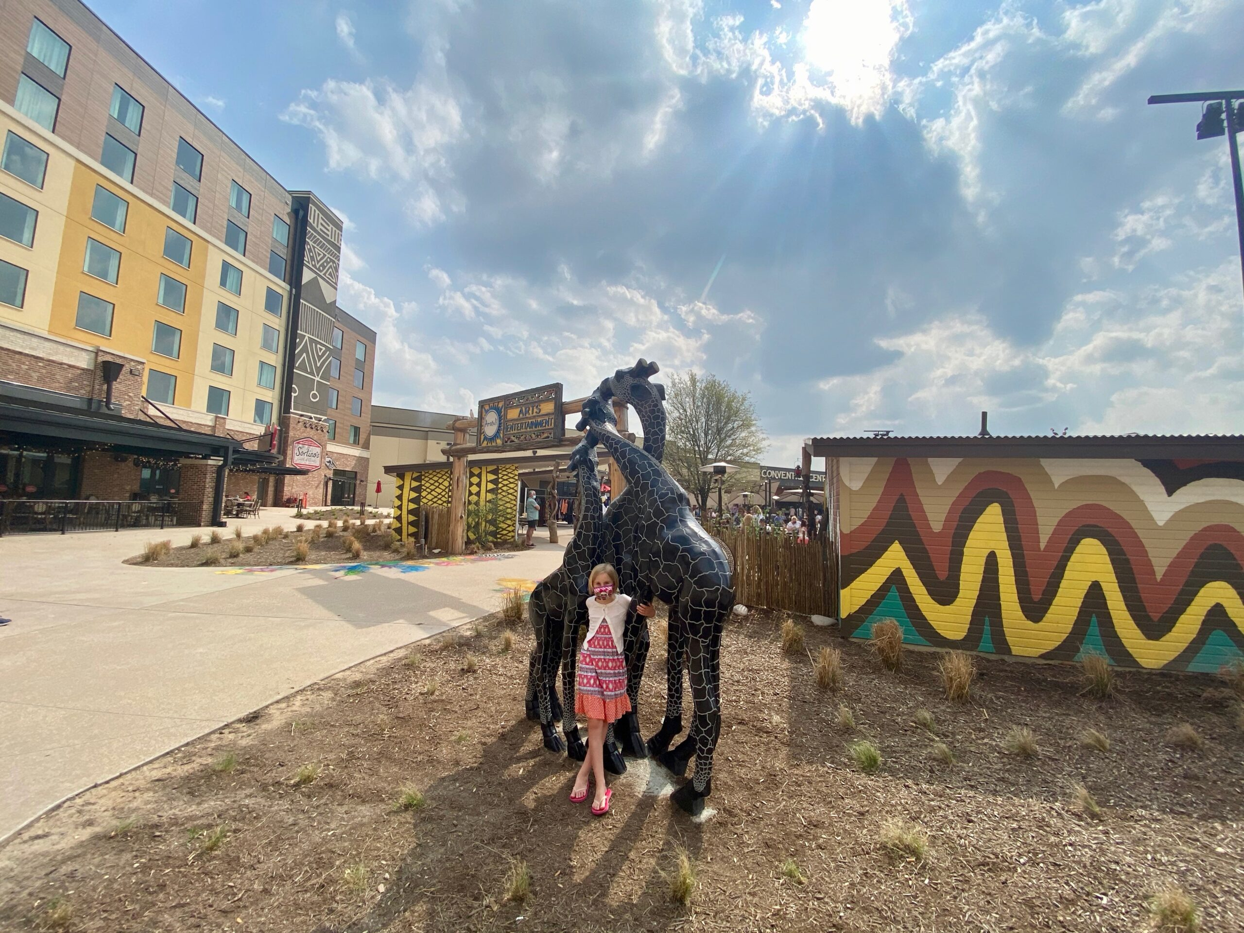 young girl posing with animal sculptures in front of the Kalahari resort in Texas