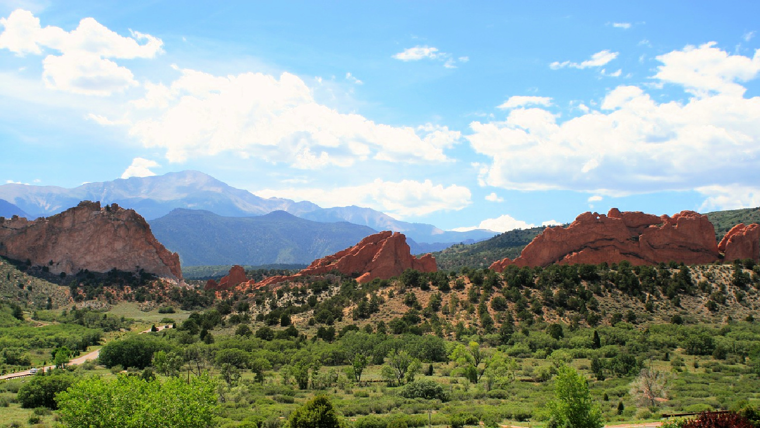 sweeping view seen from horseback of green with mountain in background at Garden of the Gods