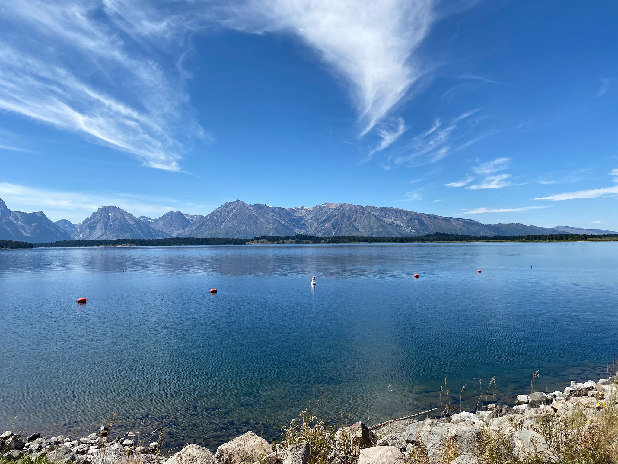 Blue sky above blue lake with mountains reflected in the water in Grand Teton NP