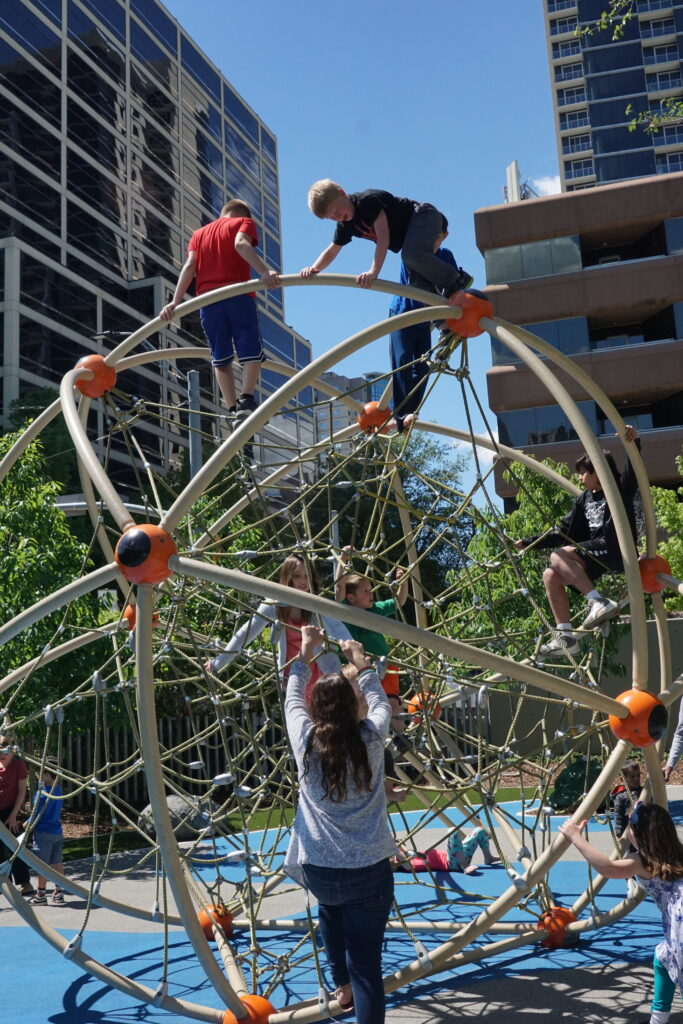 Kids playing on a climbing structure at Klyde Warren Park, one of the best things to do with kids in Dallas.