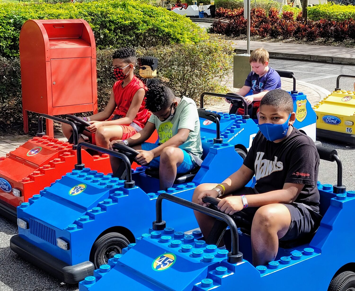 Tween children riding red and blue lego cars in the Driving School ride at LEGOLAND