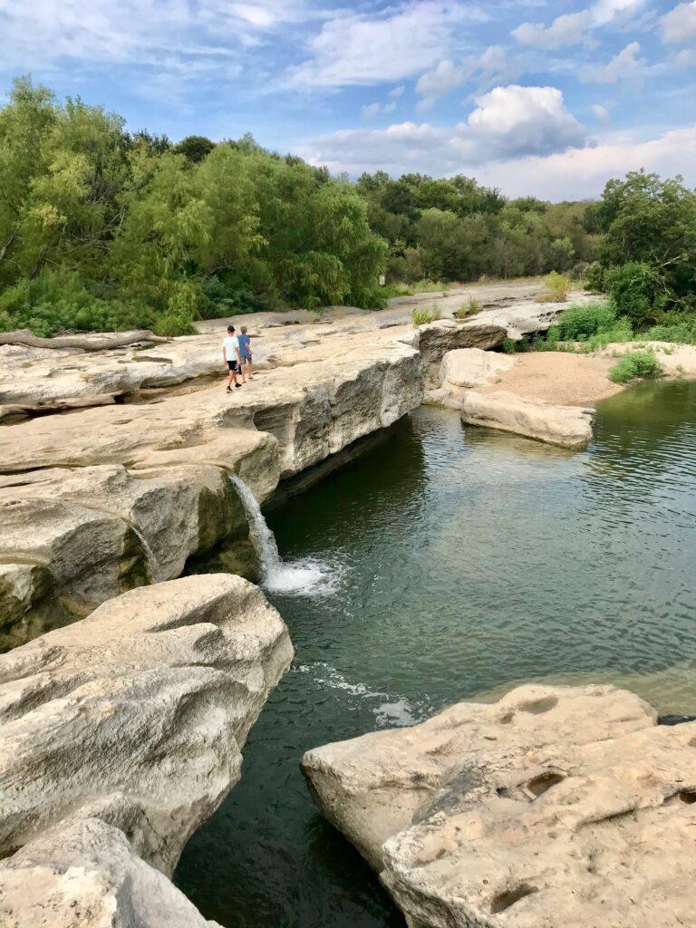 boys walking past a waterfall at McKinney Falls Park, one of the best things to do in Austin with kids.