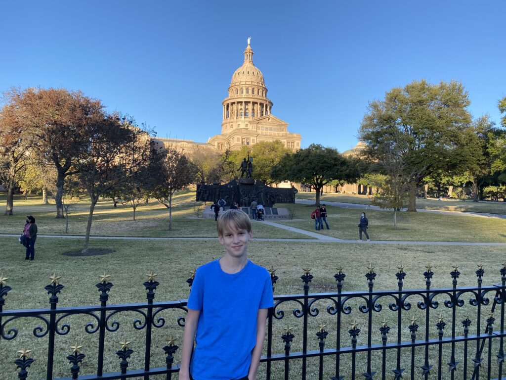 Boy in front of the Texas State Capitol
