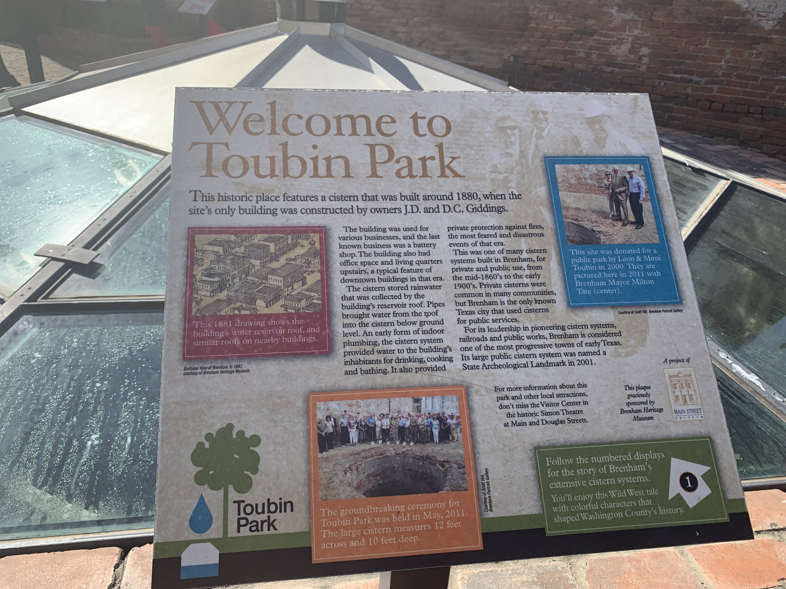 signage talking about toubin park brenham in front of a glass covered cistern