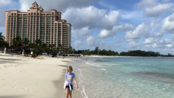 Girl walking on the beach by The Cove at the Atlantis Resort in The Bahamas.