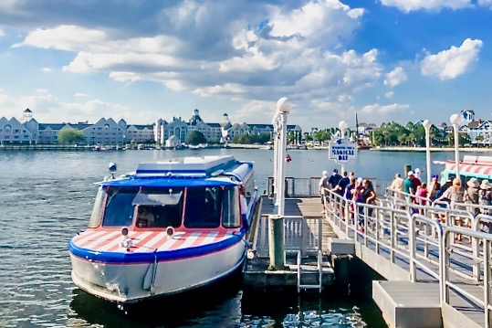 Striped blue and pink boat loading passengers traveling to Disney's BoardWalk