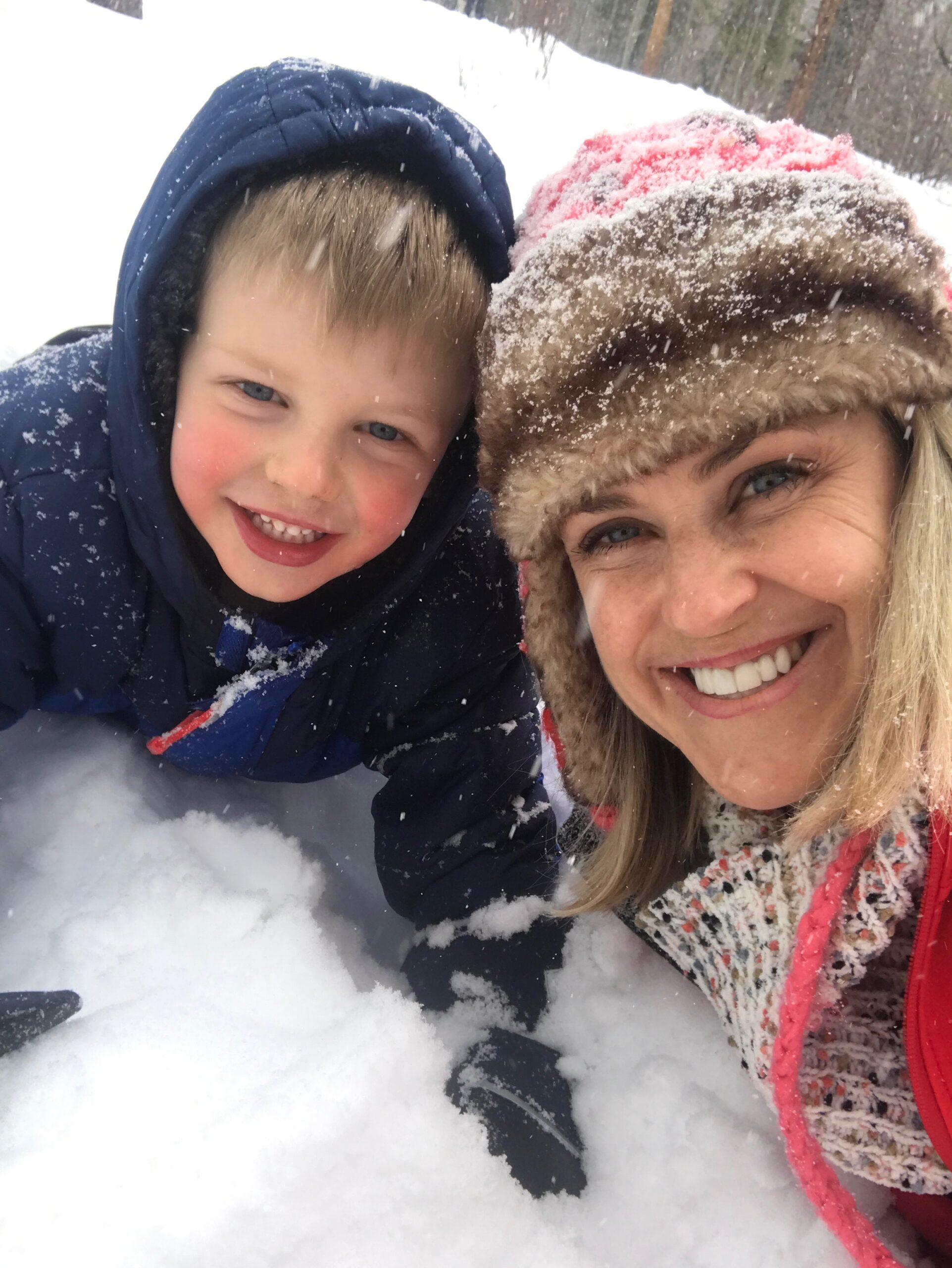 smiling child and mother in the snow near Rainbow Lake in Frisco, Colorado