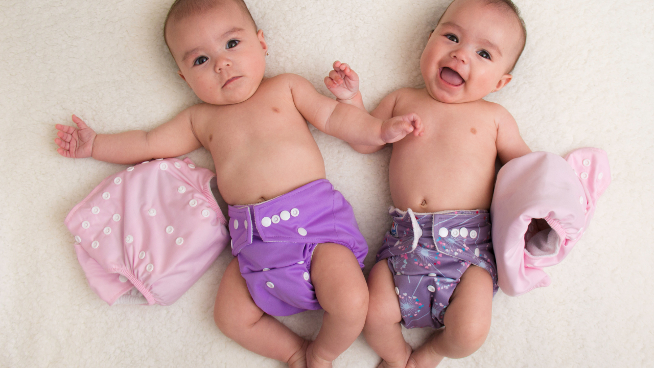 two twin babies looking up at camera. They are both wearing cloth all in one snap style diapers in purple shades.