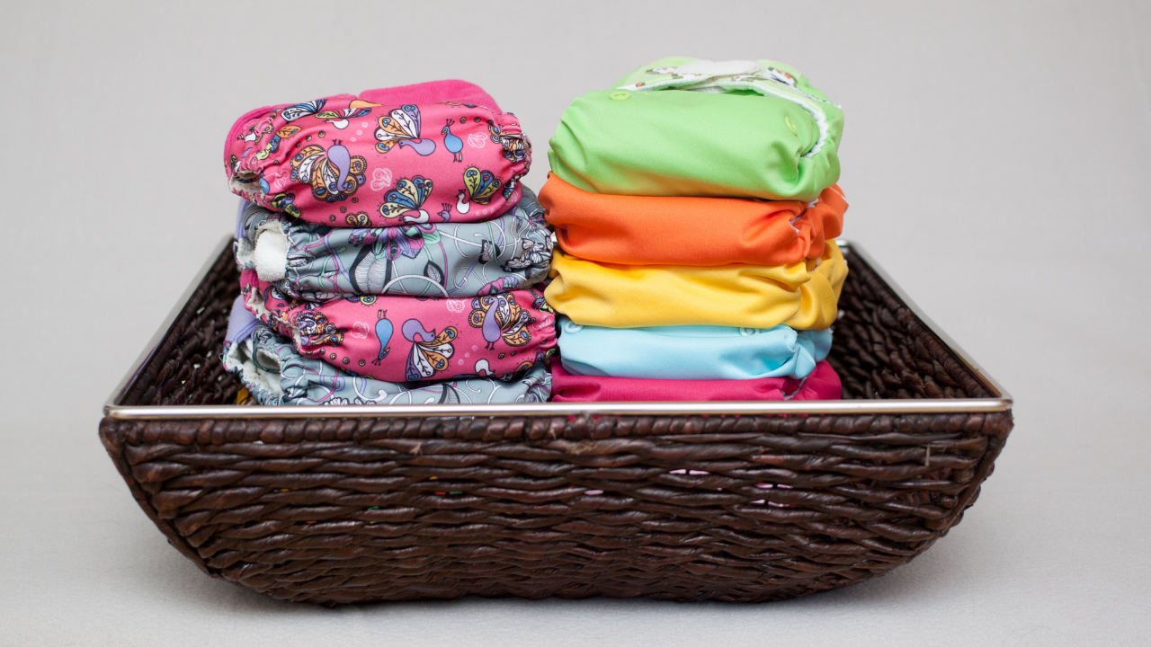 a dark brown basket filled with cloth diapers in bright colors and patterns