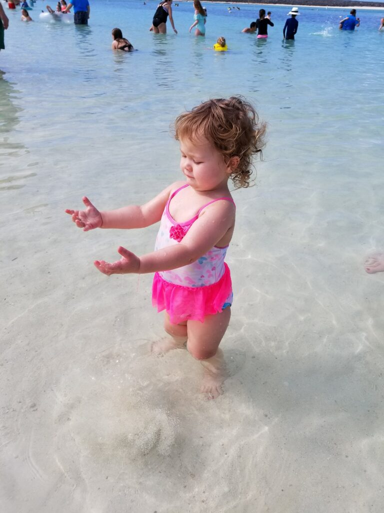 My toddler granddaughter's first ocean experience was one a Disney Cruise at Castaway Cay in The Bahamas' beaches. Photo