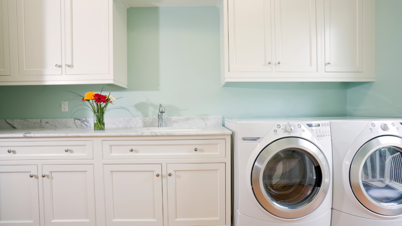 modern looking laundry room with aqua walls with white cabinets