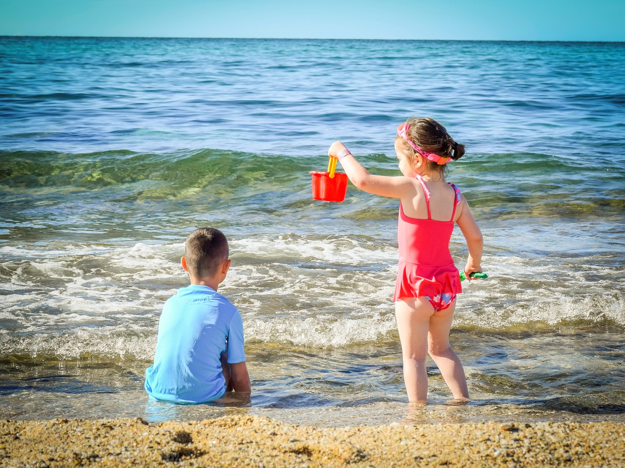 Two children playing at the beach.