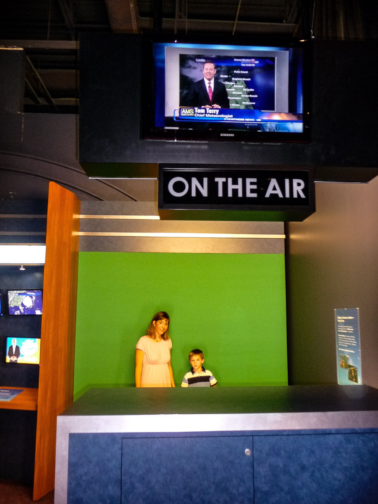 mom and son participating in a weather broadcast at the Orlando Science Center, a fun thing to do with kids
