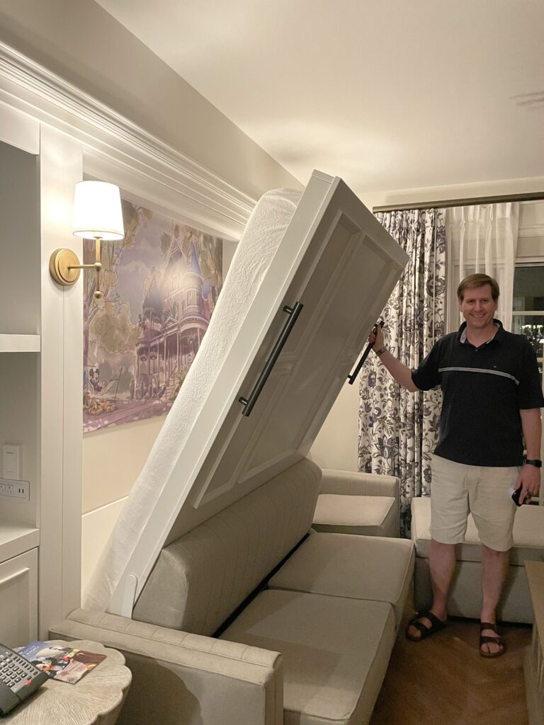 man shows off Murphy bed at Disney's Saratoga Springs