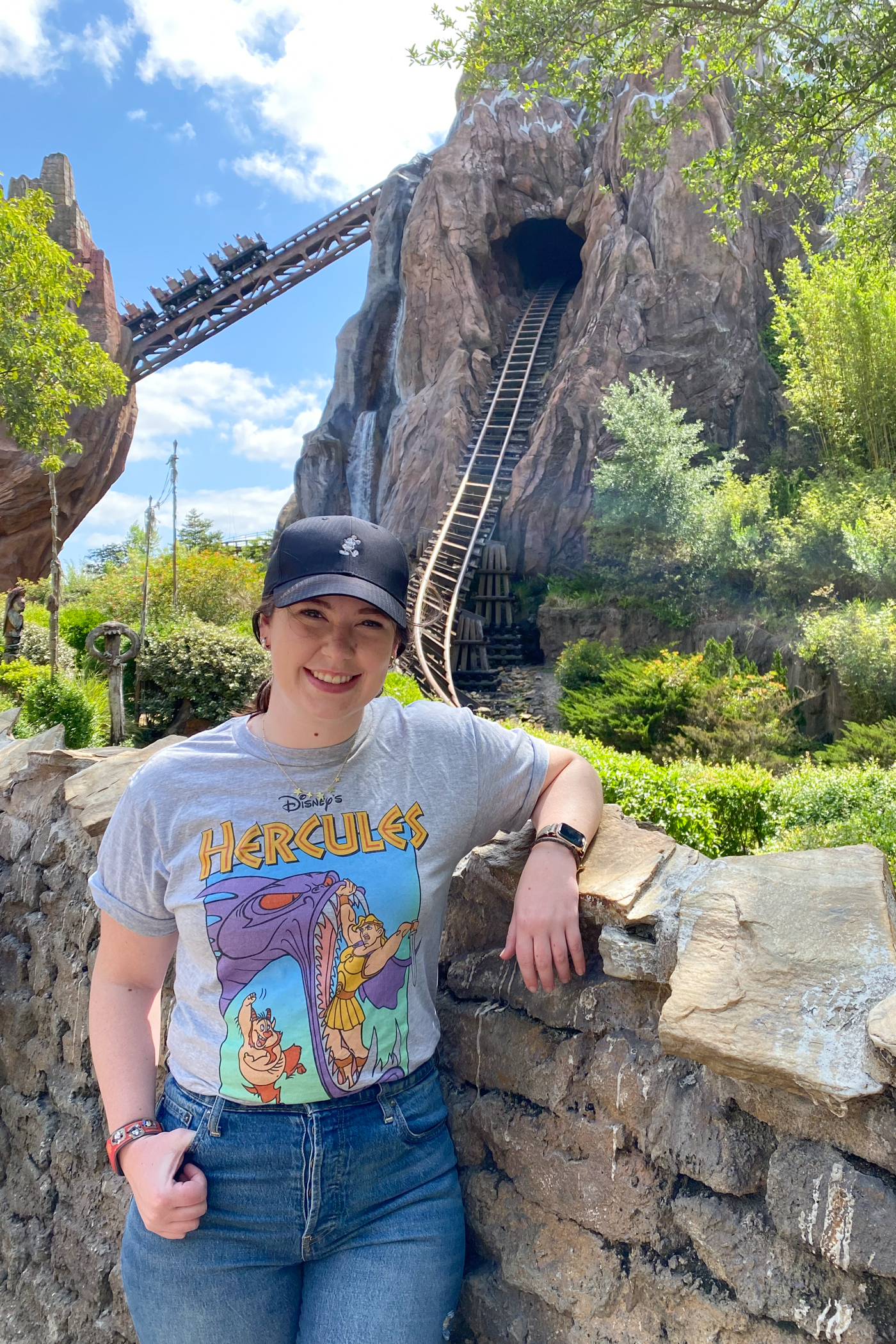 girl in hat and disney tshirt posing in front of expedition everest