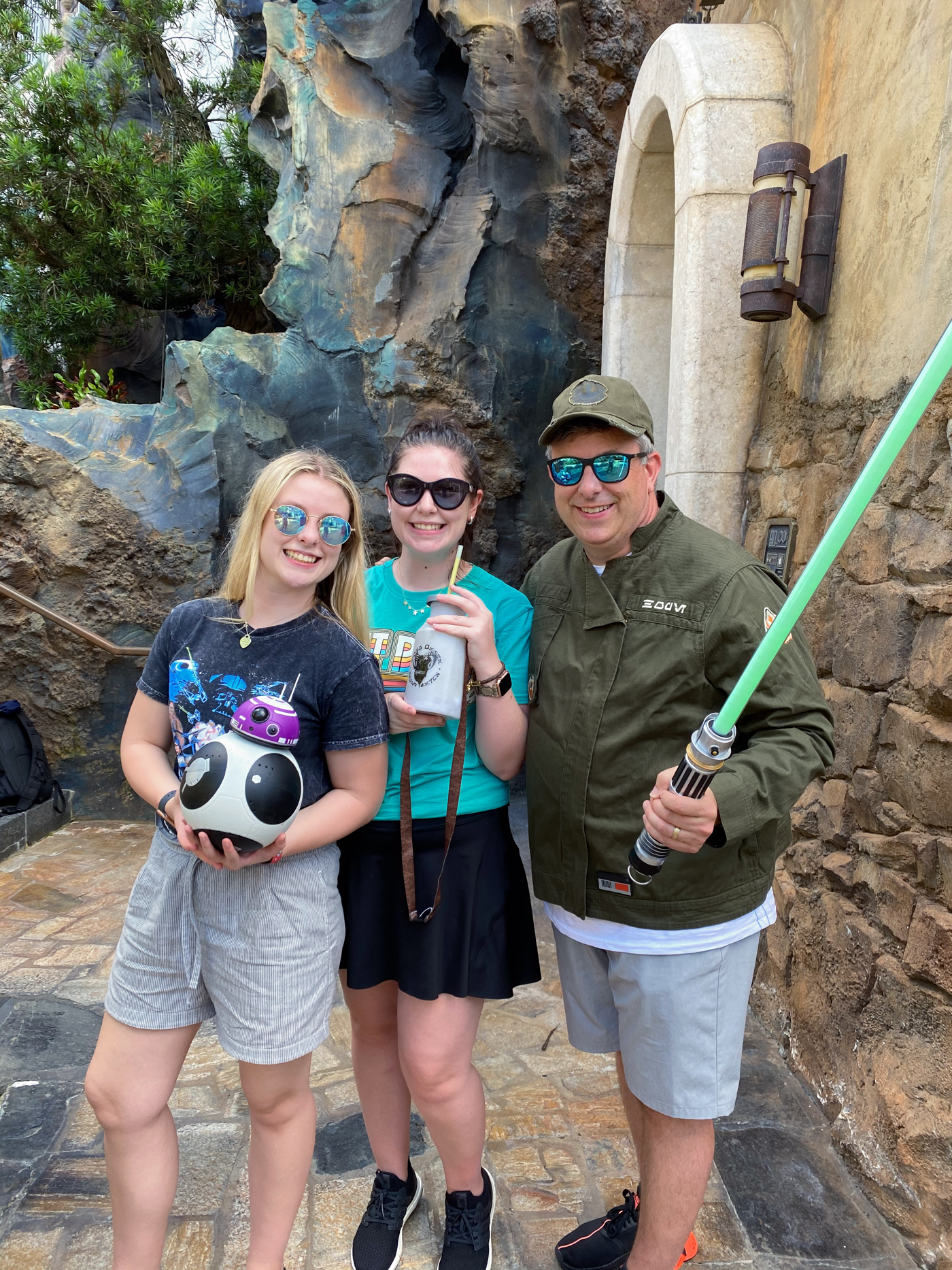 two daughters and dad holding light saber at hollywood studios