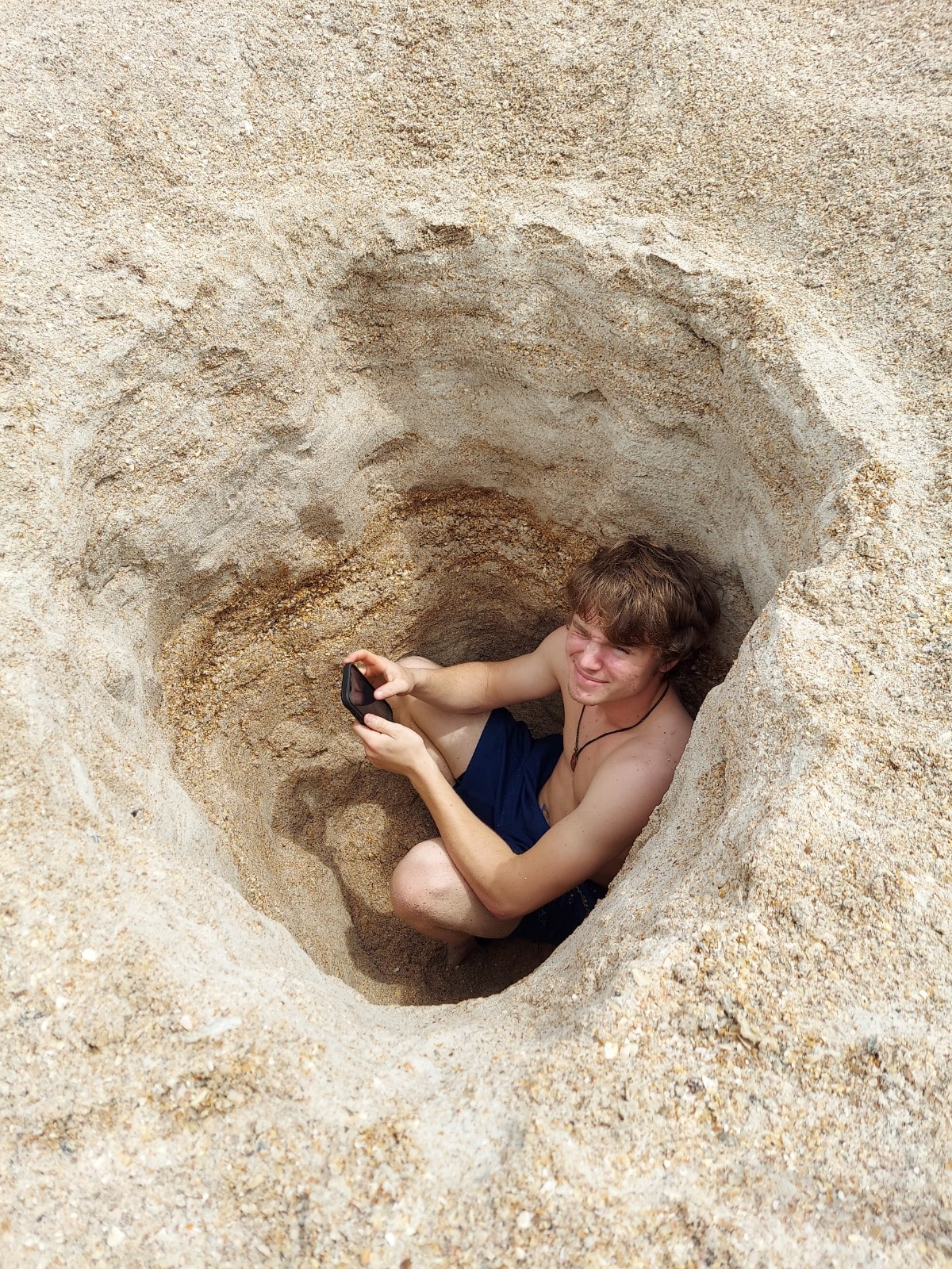 Kids digging holes in the sand on the beach in St. Augustine.