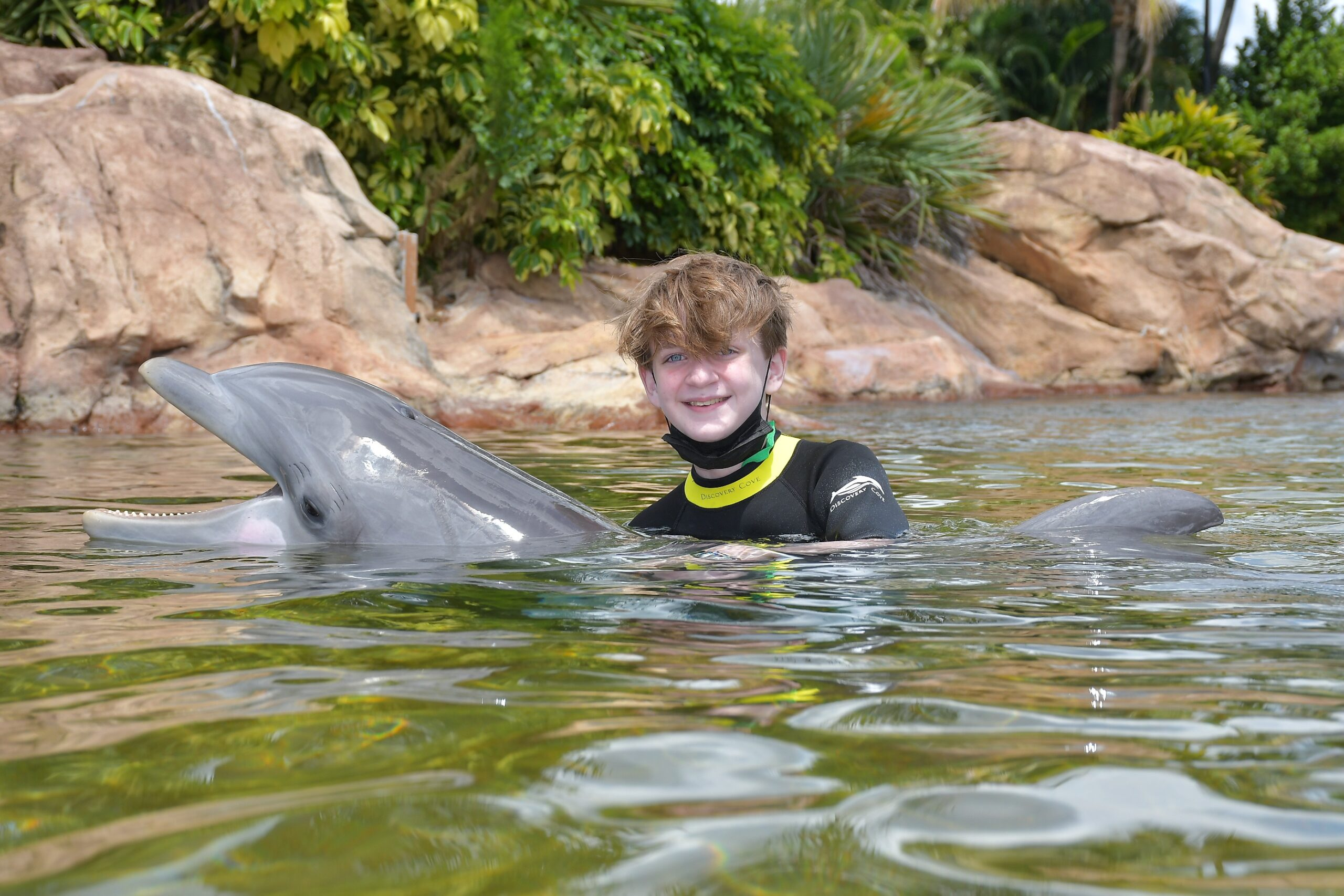 teenage boy at Discovery Cove Orlando with a dolphin as part the Dolphin Experience