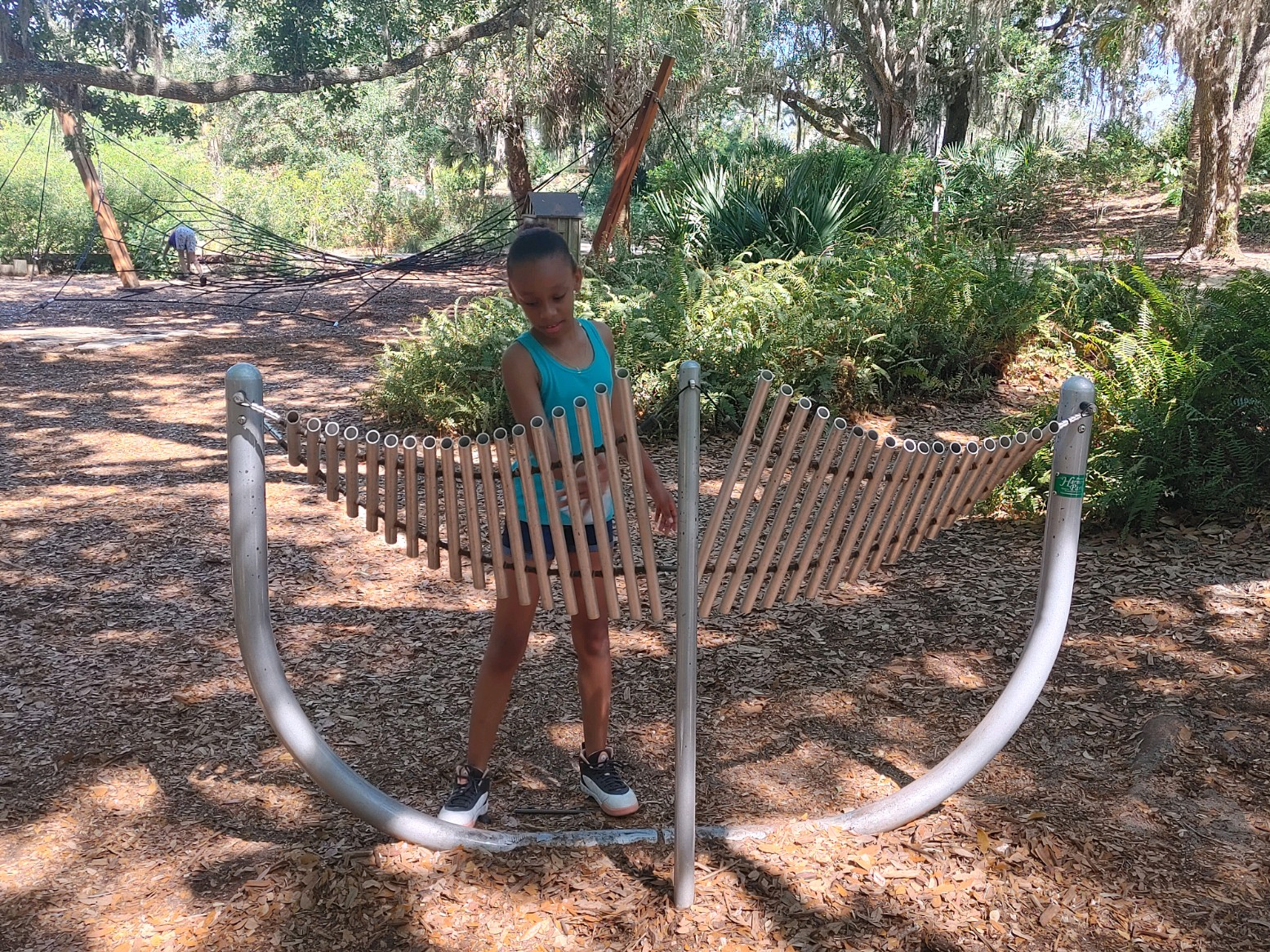 young african american girl playing outdoor xylophone type musical instrument at bok tower gardens
