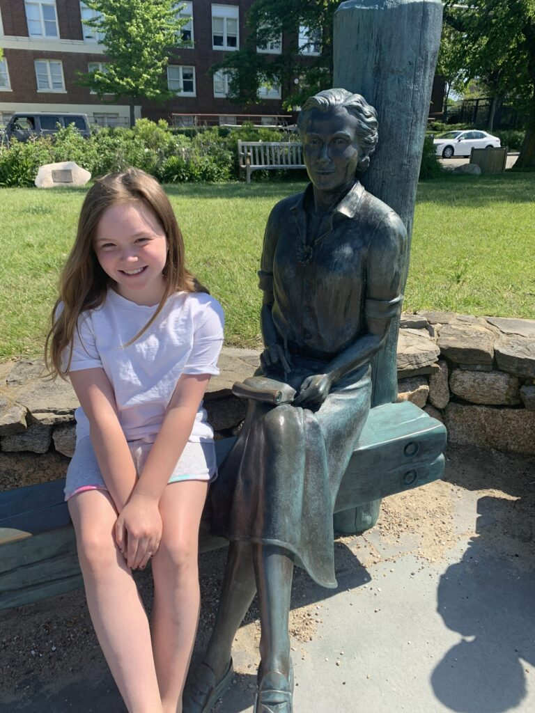 Girl posing with the statue of Rachel Carson (author of Silent Spring) that sits on a bench in a pocket-sized waterfront park in Woods Hole.
