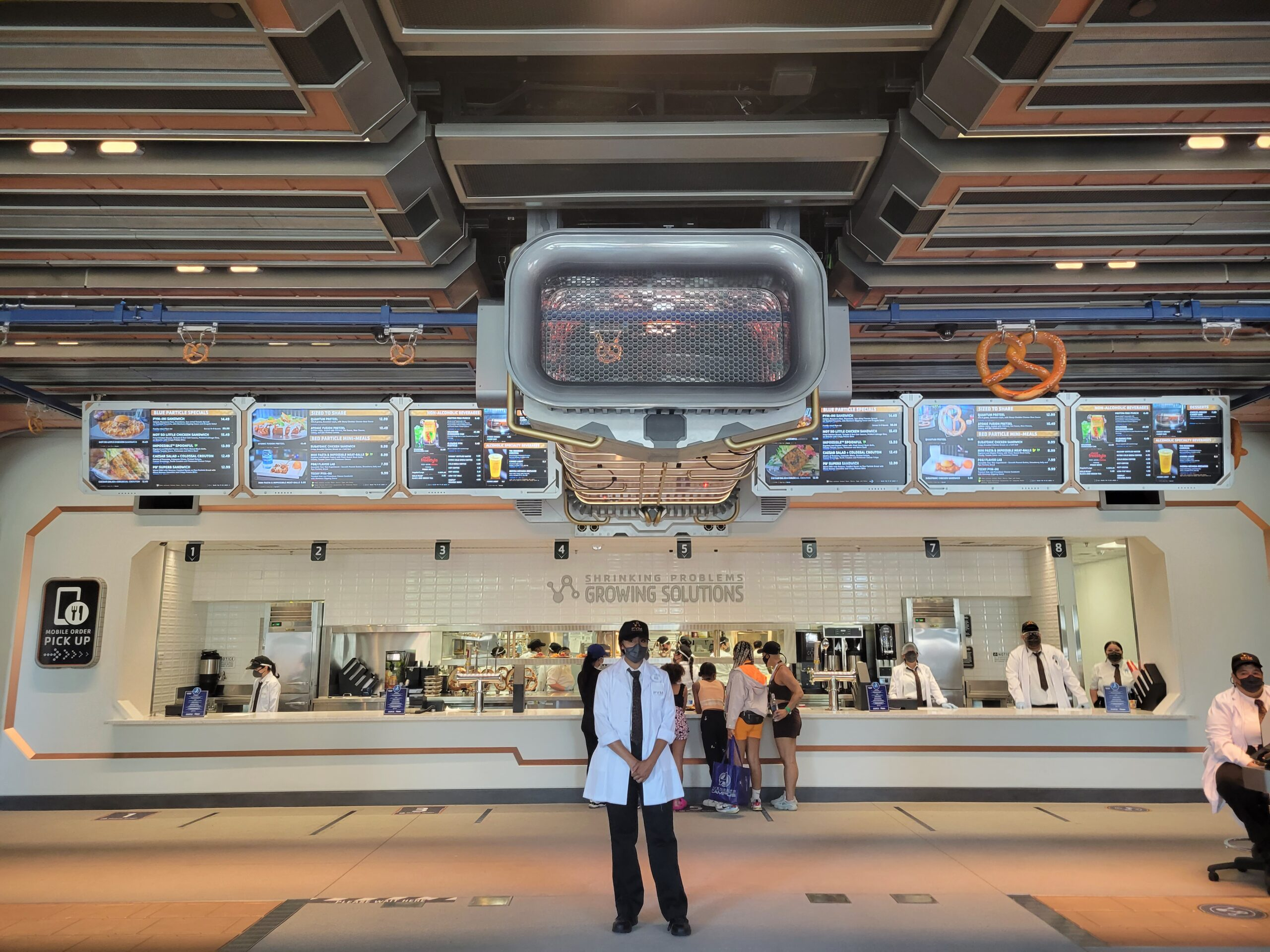 A woman in front of Pym Test Kitchen, the quick service dining at Avengers Campus Disneyland