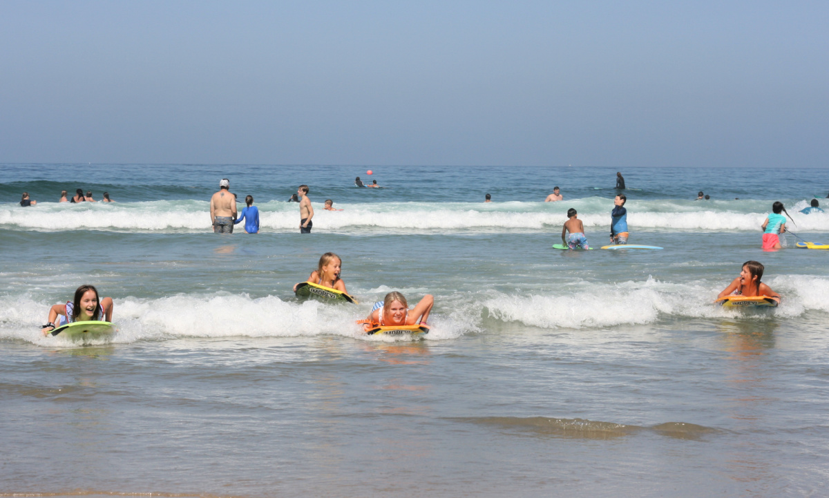 children riding boogie boards in San Diego, one of the best free things to do
