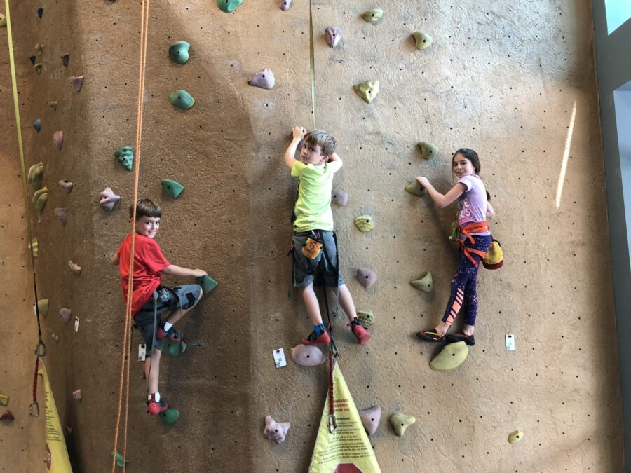 Three children climbing a rock wall, one of the fun things to do in Chattanooga with kids