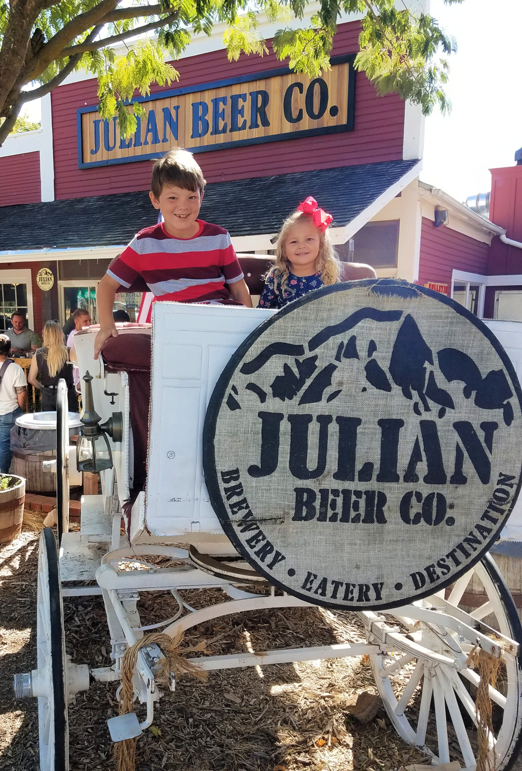 Young boy and girl in wooden wagon at the Julian Beer Co. near San Diego